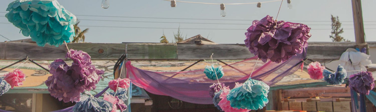 Colorful paper pom poms hanging from roof on string