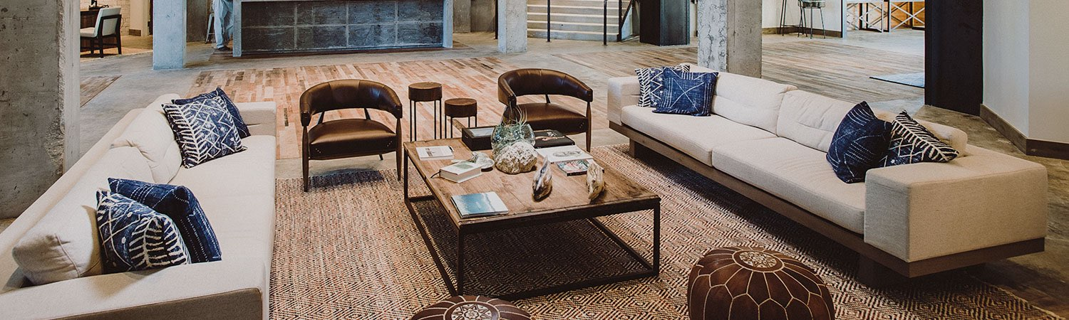 Living space with wicker rug, wooden coffee table & beige sofas with blue throw pillows