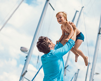 man lifting a child in front of sails
