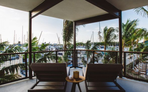 wooden chairs on balcony overlooking marina