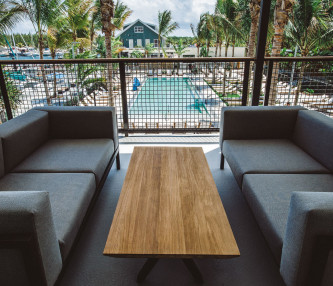 gray sofas and brown table overlooking pool
