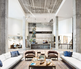 white sofas and blue accent chairs in industrial space