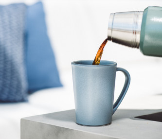 coffee cup pouring into a silver mug