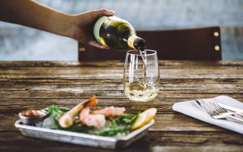 plate with shrimp and person pouring white wine