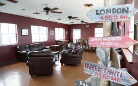 Lounge with brown leather couches and mock directional sign pointing to different cities