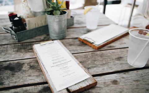 Menu on a wooden holder on a wooden table