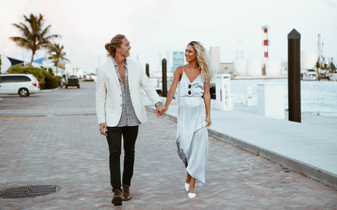Young couple holding hands walking along a marina