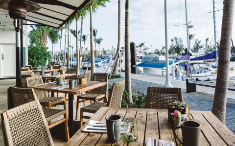 Wooden dining tables set up outside overlooking a marina
