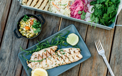 Overhead view of grilled fish with a side salad