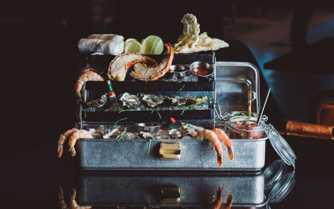 tackle box filled with seafood on black table