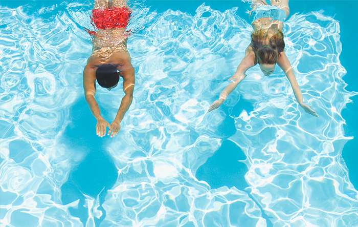 Man and woman swimming under water in swimming pool