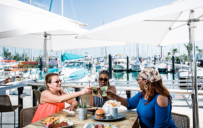 Three women toasting at outdoor table next to marina