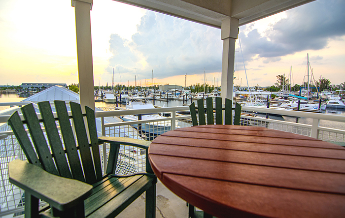 wooden table with green chair overlooking marina