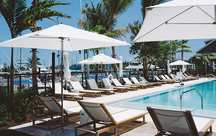 White loungers with umbrellas next to pool