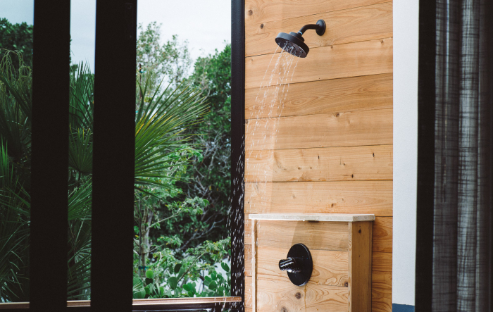 Bathroom with wooden vanity, rolled up towels next to glass door shower