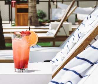 Pink cocktail with strawberries & orange wedge on table next to pool loungers