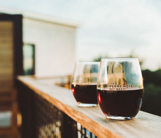 Two stemless glasses of red wine on wooden ledge