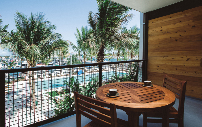 Wooden table with chairs on room balcony overlooking pool