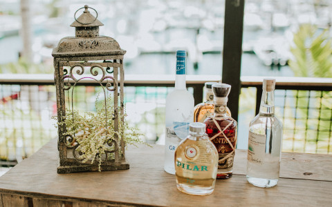 Alcohol bottles and gold lantern on wooden table overlooking marina
