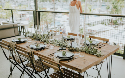 Woman overlooking marina on balcony with event table set up behind her