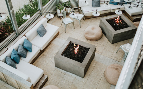 Aerial view of outdoor seating area with couches and fire pits