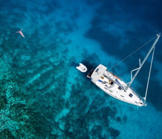 yacht sailing in blue water with woman in water floating