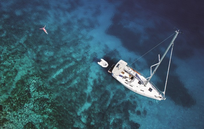 aerial shot of the ocean with a sailboat and girl floating in the water
