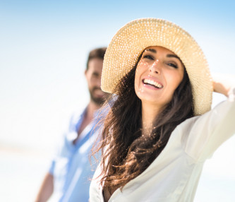 woman smiling at beach with hat