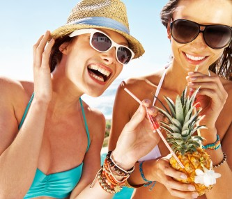 two women laughing drinking out of a pineapple in bathing suits