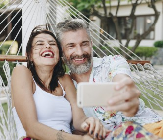 couple laughing taking a selfie on hammock