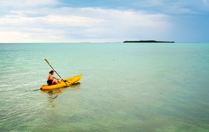 girl kayaking into open water