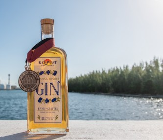 a bottle of gin with a medal and the water in the background
