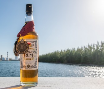 a bottle of rum with a medal and the water in the background