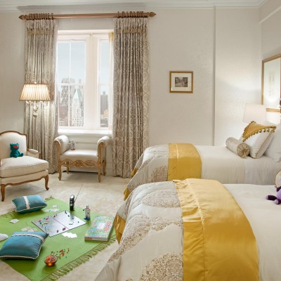Bedroom with two double beds and kid games on the floor