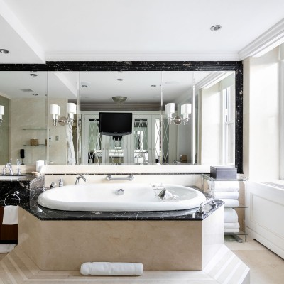 Bathroom with vanity, large mirror & marble bathtub