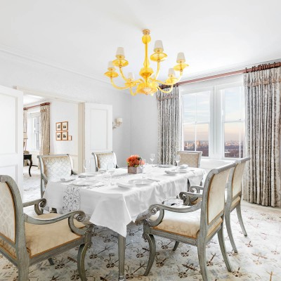 In-room dining area with gold chandelier above table