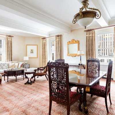 In-room dining space with patterned carpets and wooden table