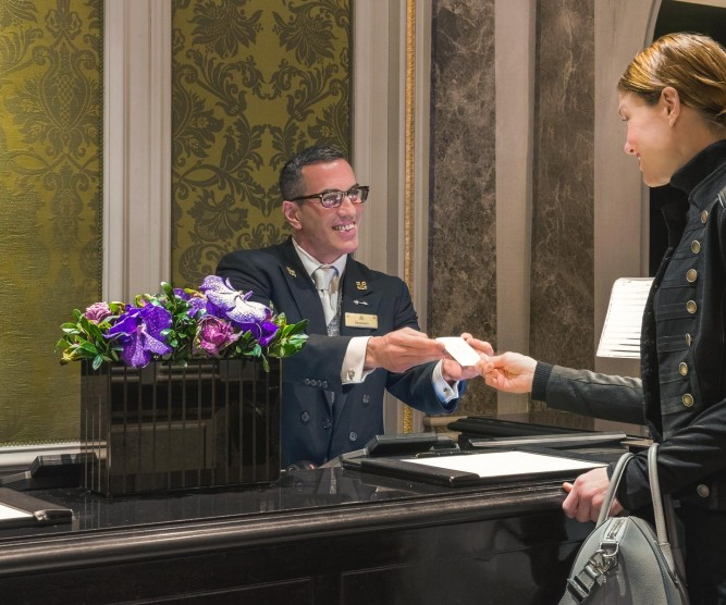Hotel staff handing guest keycard at front desk