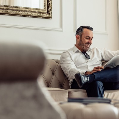 Man reading paper on sofa