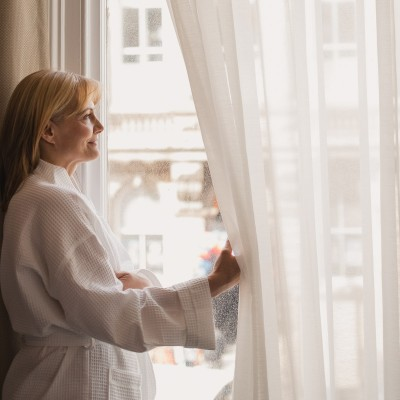 Woman in robe looking out window