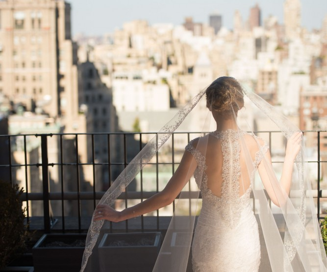 Bride with veil walking on outdoor terrace