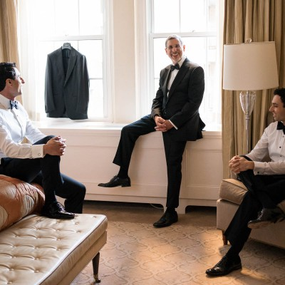 Groom sitting in room with two groomsmen