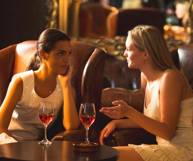 Two women in lounge drinking red wine