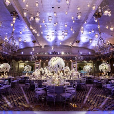 Event space with white flower centerpieces and purple lighting