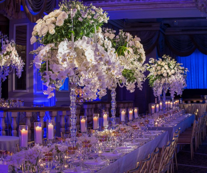 Long table set for wedding with crystal candlesticks and elaborate white floral decor