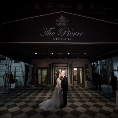 Bride and groom kissing in front of The Pierre entrance