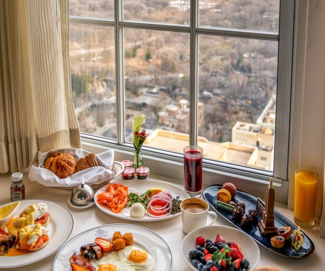 assortment of breakfast foods delivered to a room with a view of the city