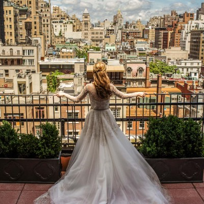 bride posing on balcony in front of skyline