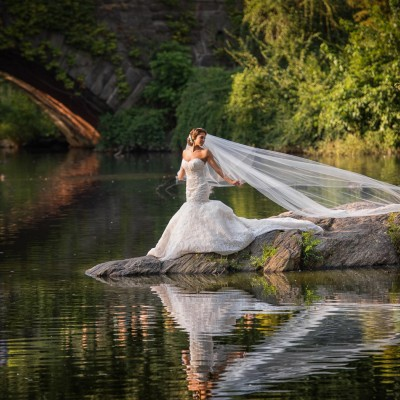 bride posing in front of lake and stone bridge