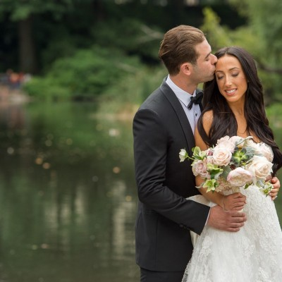 bride and groom share a kiss in front of a beautiful lake